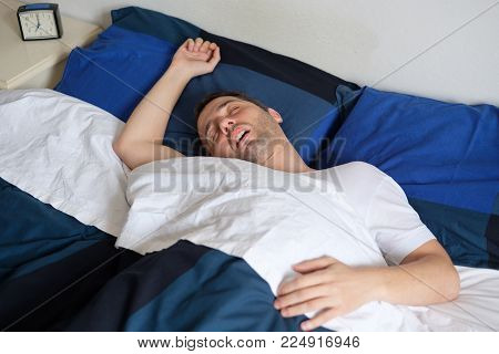 Portrait of man sleeping and snoring loudly lying in the bed