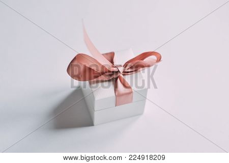 Romantic gift box on a white background. Close up shot a small gift wrapped with pink ribbon