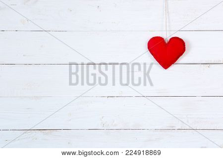 Love heart on string against white wooden texture background. Valentines day card concept.