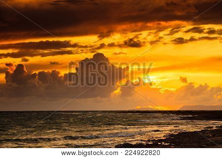 Dramatic sunset over sea surface with dark stormy clouds, Greece Peloponnese.