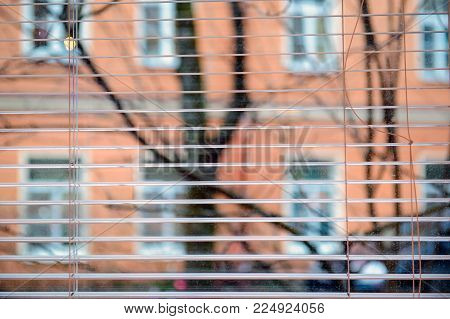 Looking out the window at the street. Windows with a view through blinds. Conceptual photo of life in the house.