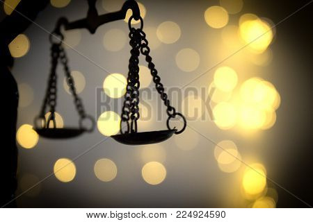 Scales of justice on bright lights background