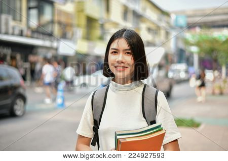 Education Concepts. Asian women reading books in the city. Beautiful women are relaxing in the city. Beautiful women are happy to read.  Asian girls love to study. Education of Asian Women.