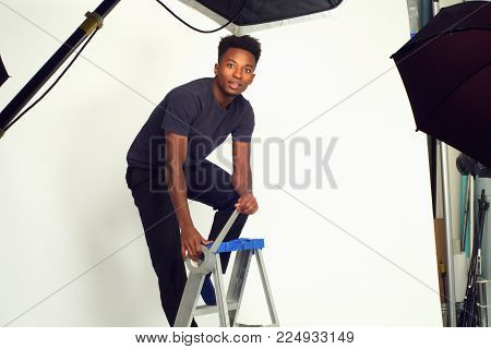 young technician photographer working in studio fixing with duct tape
