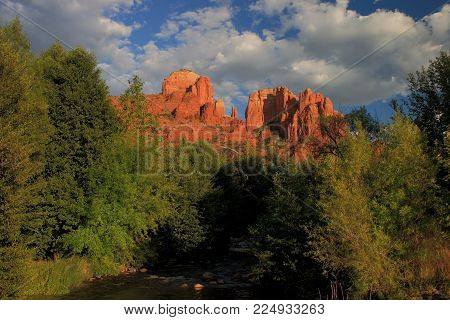 Cathedral Rock, Sedona, Arizona as the sun was getting low in the sky causing the rock to glow in comparison with the foreground foliage and the blue sky background with several clouds.