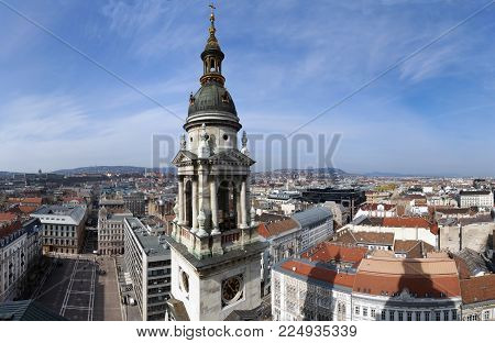 panoramic view of budapest from the cathedral showing the bell tower and spire the main square and ariel view of the city with mountains in the background and blue sky