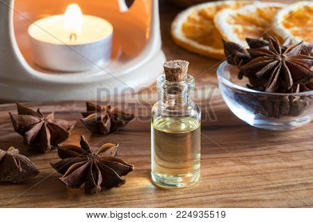 A bottle of star anise essential oil with star anise and an candle in the background
