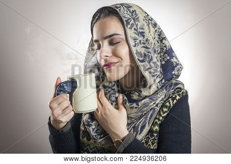 Young beautiful woman enjoying the smell of her favorite hot drink, tea or coffee