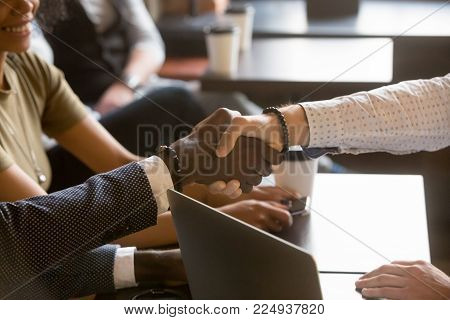 Multiracial men handshaking in coffee house, black and white hands shaking over cafe table, diverse businessmen making deal reaching agreement at meeting in coffeeshop with laptop, close up view