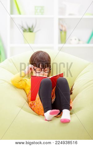 Little Wise Girl With Glasses Reading From Book