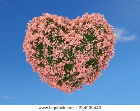 Heart shape covered with grass and pink flowers on blue sky