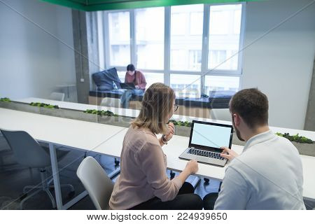 A man and a girl work as a team at a computer in the work space. Discussion of work processes. Work in coworking