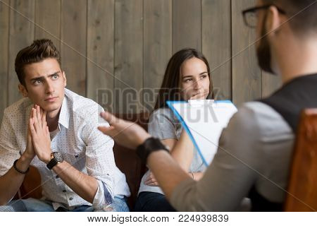 Frustrated young man listening to psychologist while his offended girlfriend sitting apart, family counselor talking to unhappy couple solving problems in relationships at counseling therapy session