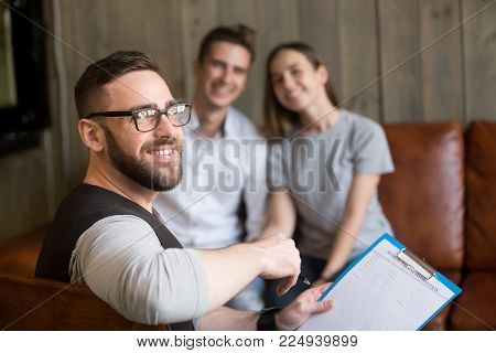Smiling professional man psychologist consulting young couple, friendly psychotherapist or marriage counselor expert looking at camera counseling clients in office, family therapy concept, portrait