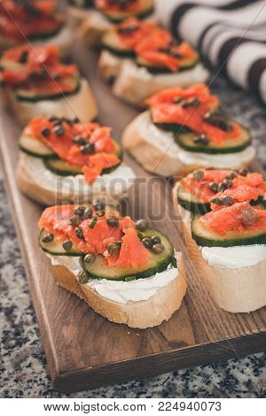 Several finger sandwiches with smoked salmon and cream cheese cover a cutting board.  Capers and sliced cucumber are included on the sandwiches.