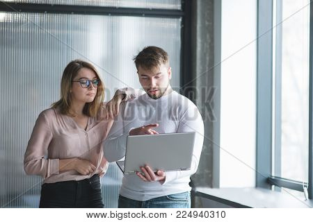Office workers use a laptop on the background of the wall. A husband discusses work with a woman standing at the background of the office wall