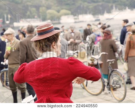 STOCKHOLM - SEPT 23, 2017: Rear view of woman dressed in red cardigan from aprox 1940 and a straw hat  in the Bike in Tweed event September 23, 2017 in Stockholm, Sweden