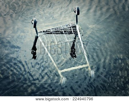 Shopping cart illegal disposed of in the sea as waste with black and white colors and light waves