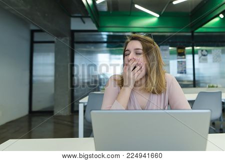 The office worker sits at the office in the office behind a laptop and yawns. A tired girl works for a computer in a modern office.
