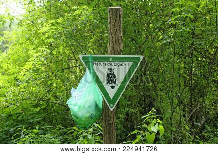 Waste in the nature reserve - warning sign Nature reserve to which a bag with garbage was hung