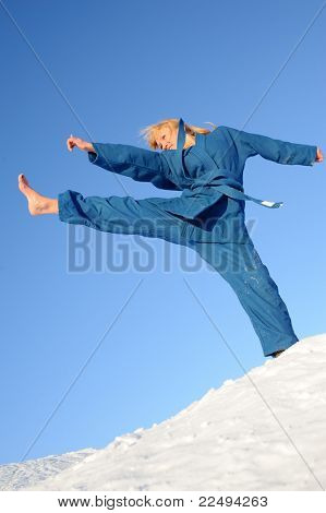 young woman in blue uniform training combat sport outdoors in winter, barefoot on the snow