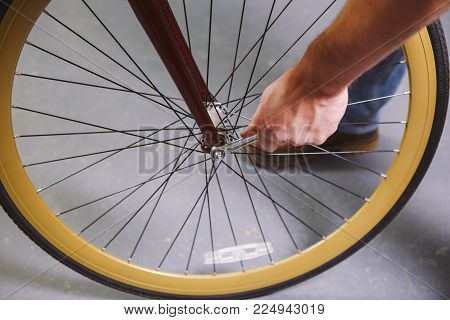 Theme repair bikes. Close-up of a Caucasian man's hand use a hand tool Bike Tools Hub Cone Wrenc to adjust and install Quick Releases and Thru Axles on a red bicycle.