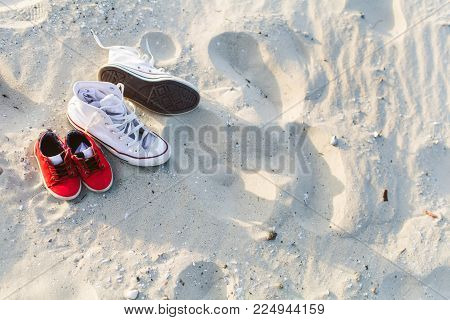 Two pairs of gumshoes, mom and son, red and white, stand on the sand at a sunset beach