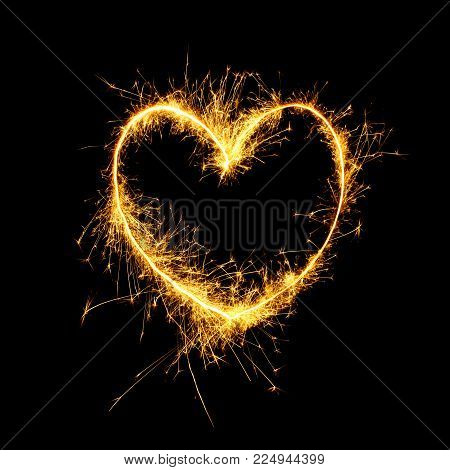 Beautiful Sparkling golden heart isolated on black background. Glowing Outline of a heart shape to overlay on the textures in the design Holiday greeting card, background for Valentine's Day, Wedding