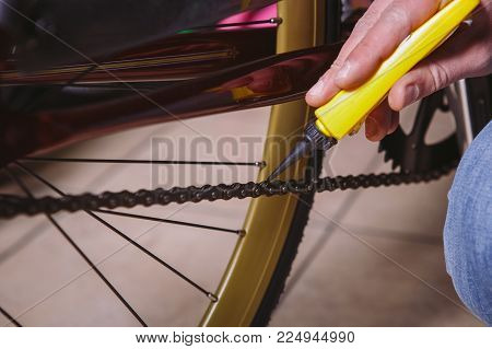 Theme Repair Bikes. Close-up Of A Caucasian Man's Hand Use A Chain Lubricant In A Yellow Lubricator