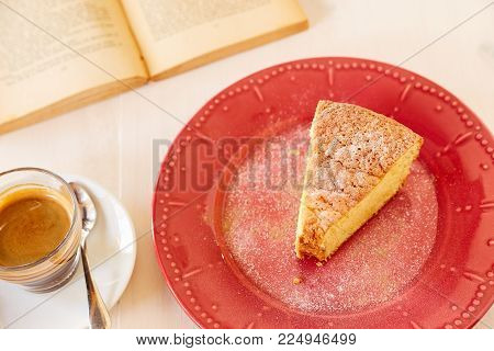 Homemade pie on a ceramic plate on a white wooden table. A piece of delicious carrot pie on a red shiny plate and vintage old book. Part of a homemade cupcake on a plate with black coffee.