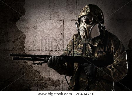 armed soldier with gas mask wearing a camouflage uniform against a wall poster