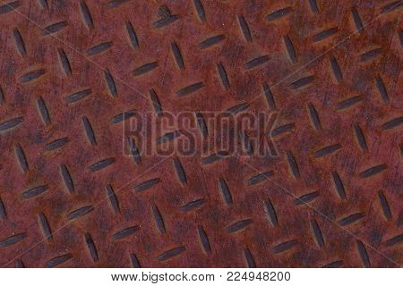 Rusted red diamond plate close up abstract texture background.