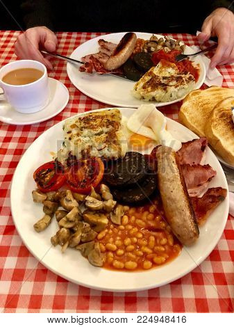 Full English fried breakfast with bacon, sausage, eggs, tomatoes, black pudding, mushrooms, beans and bubble & squeak in a greasy spoon cafe
