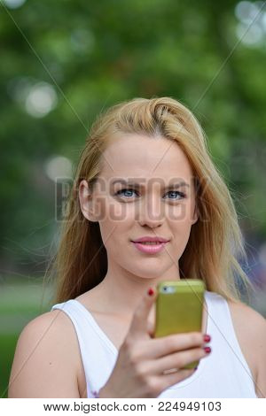 Young, beautiful blonde girl outdoors in summer time, holding smart phone, smiling and taking photo