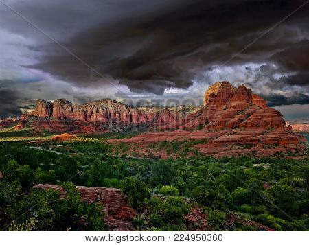 Bell Rock in Sedona Arizona with a swirling vortex of clouds overhead. Tornadoes in Arizona are very rare with an average of 3 to 5 per year, but these partial funnel clouds can be quite common.