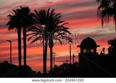 Dramatic red and purple streaked clouds fill the sky at sunset, with palm trees and a cupola silhouetted against the evening sky.