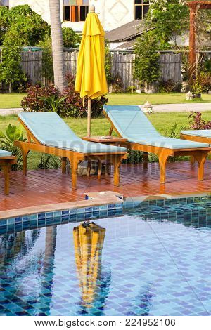 Chaise lounges and yellow umbrella next to the swimming pool in the morning, Thailand