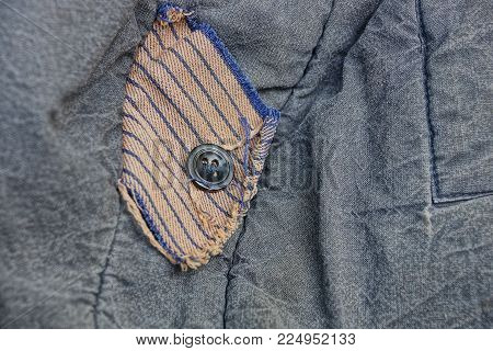 black button on a piece of cloth on clothes