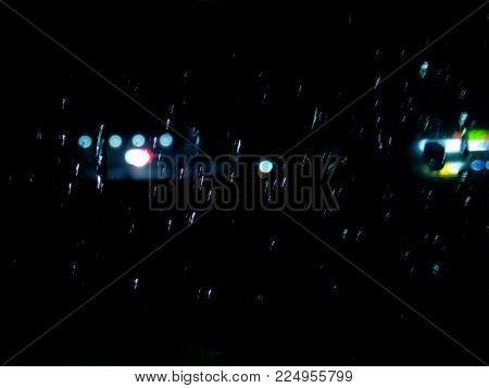 Night rain in the window drops of rain on the glass city lights in the dark time of the day blurred background