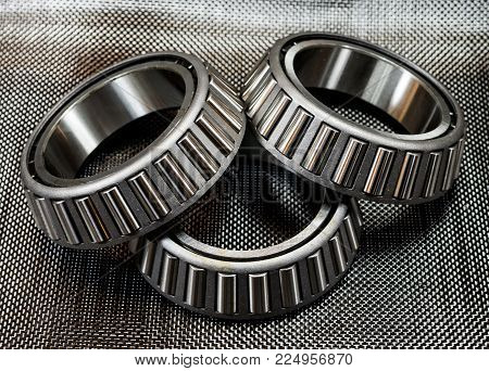 3 antique automotive tapered roller bearings on plain weave carbon fiber.