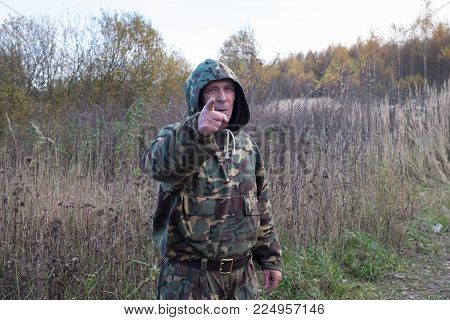Old man in suit camouflage colors in autumn woods. He looks straight ahead and index finger pointing straight. In the background of autumn forest.