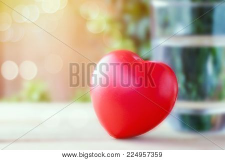 red heart and glass of water on wood