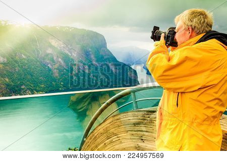 Tourism and travel. Male tourist nature photographer taking photo with camera, enjoying Aurland fjord landscape from Stegastein lookout, Norway Scandinavia.