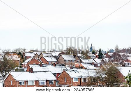 Cloudy Day Winter View of Row of Typical English Terraced Houses under snow in Northampton.