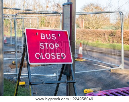Day view sign informing about roadworks next to bus stop on UK road.
