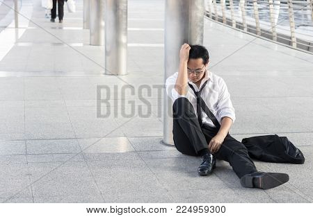 desperate and unemployed people, Economic downturn concept, frustrated man sitting on street, walkway after finding no job