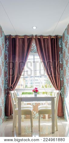 flowers on white dining table in livingroom of hotel room, outside window to city view