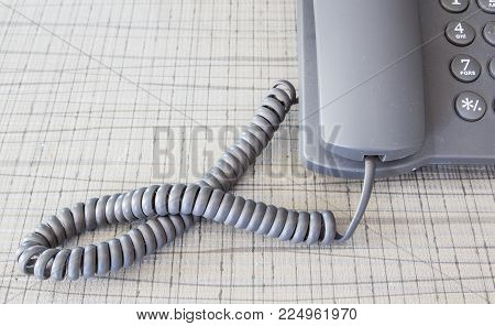 old and dirty grey telephone on the tablecloth of desk