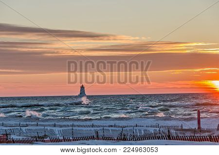 Ludington, Michigan's North Breakwater Light with a beautiful sunset and blue green waves with whitecaps crashing in to the shore