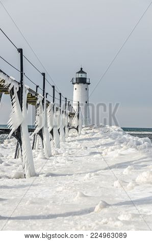 Manistee North Pierhead Lighthouse on Lake Michigan with icicles that look like fringe hanging from the catwalk